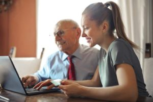 Old man on laptop with young girl, paying bills