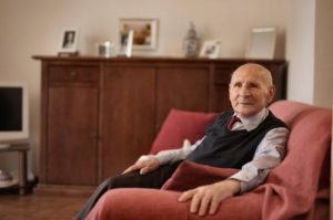 Old man sitting on a sofa alone